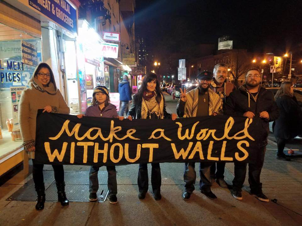 "A group holds a sign saying ""Make a world without walls"""